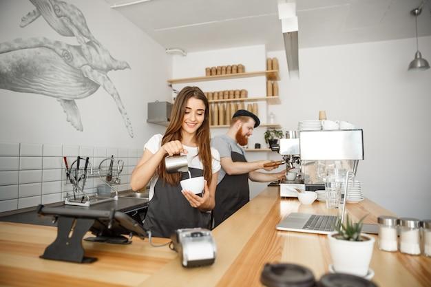 Café concept d'affaires - close-up lady barista dans le tablier préparant et versant du lait dans une tasse chaude tout en restant au café.