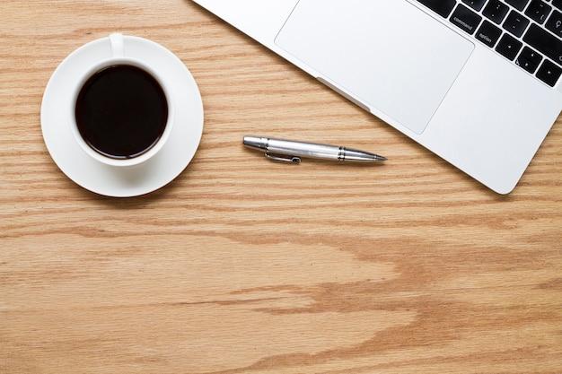 Café à côté d'un stylo et d'un ordinateur portable