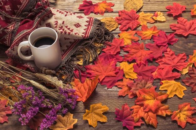 Café et couverture près des feuilles et des fleurs
