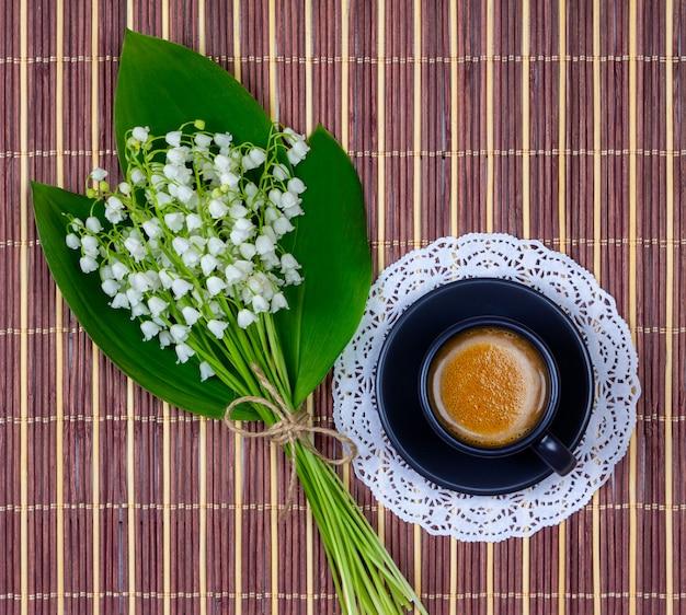Café à la crème dans une tasse noire sur une soucoupe et un bouquet de fleurs de muguet à feuilles vertes