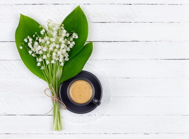 Café à la crème dans une tasse noire sur une soucoupe et un bouquet de fleurs de muguet