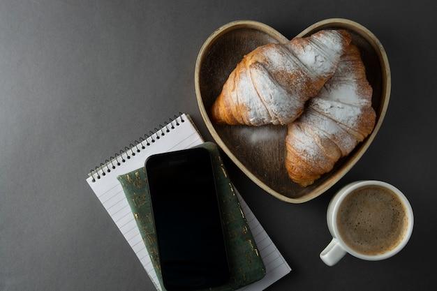 Café avec croissant dans une boîte en bois en forme de coeur. espace de copie.