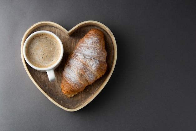 Café avec croissant dans une boîte en bois en forme de coeur.