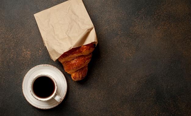 Café et croissant sur un fond de pierre. petit déjeuner savoureux avec espace de copie pour votre texte