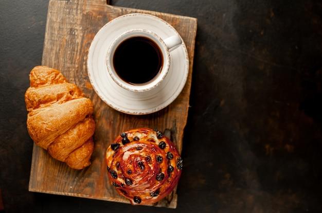 Café et croissant, pain sur une table en pierre. petit déjeuner le matin, avec copie espace pour le texte