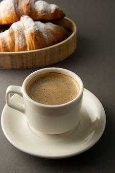 Café avec croissant sur la table de travail, petit-déjeuner au travail.