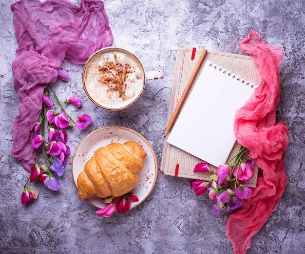 Café, croissants, fleurs et cahier.