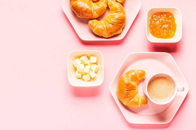 Café et croissants pour le petit déjeuner sur fond rose, vue de dessus, mise à plat.