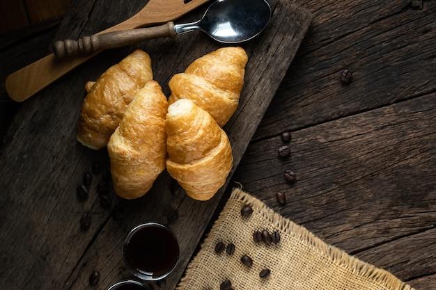 Café et croissants sur la surface en bois