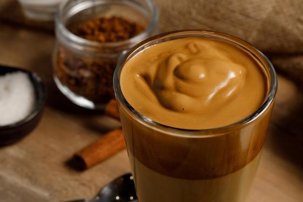 Café dalgona - la boisson au café coréenne sur fond de bois. café instantané ou poudre d'espresso fouetté avec du sucre et de l'eau chaude. concept de café dalgona fouetté glacé.