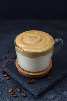 Café dalgona dans un capuchon en verre sur fond sombre. lait avec du café fouetté crémeux et moelleux.