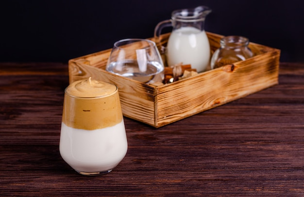 Café dalgona avec des ingrédients pour la préparation dans une boîte sur un fond en bois