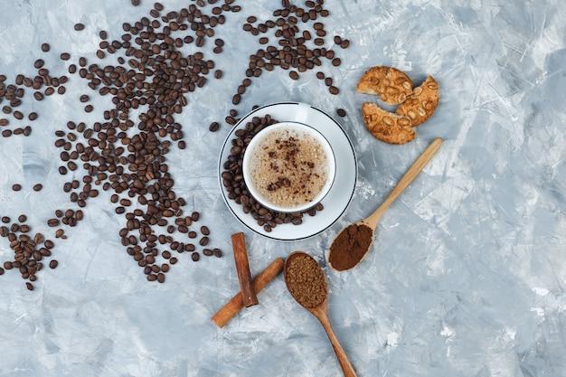 Café dans une tasse avec des biscuits, des grains de café, du café moulu, des bâtons de cannelle vue de dessus sur un fond de plâtre gris