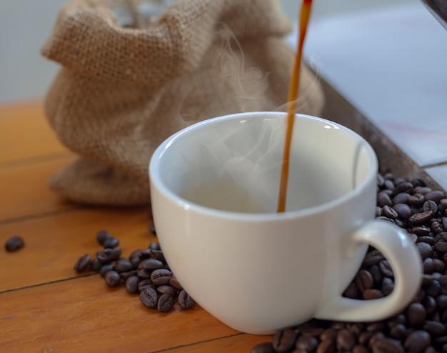 Café dans une tasse blanche et grains de café sur une table en bois