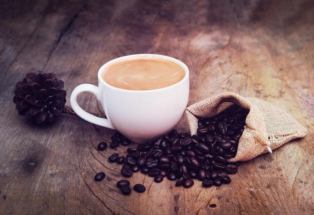 Café dans une tasse blanche avec des grains de café sur une table en bois