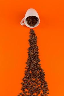 Café dans une tasse blanche sur une surface orange avec des grains de café.