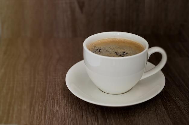 Café dans une tasse blanche sur la table.