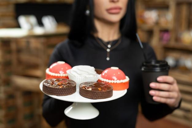 Café dans une tasse en carton et desserts sur un plateau gros plan entre les mains d'une femme.