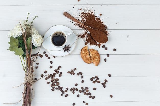 Café dans une tasse avec du café moulu, des épices, des fleurs, des grains de café, des biscuits à plat sur un fond en bois