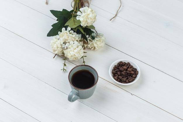 Café dans une tasse avec des grains de café, des fleurs vue grand angle sur un fond en bois