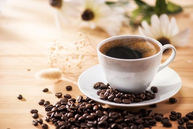 Café dans une tasse et grains de café avec des fleurs
