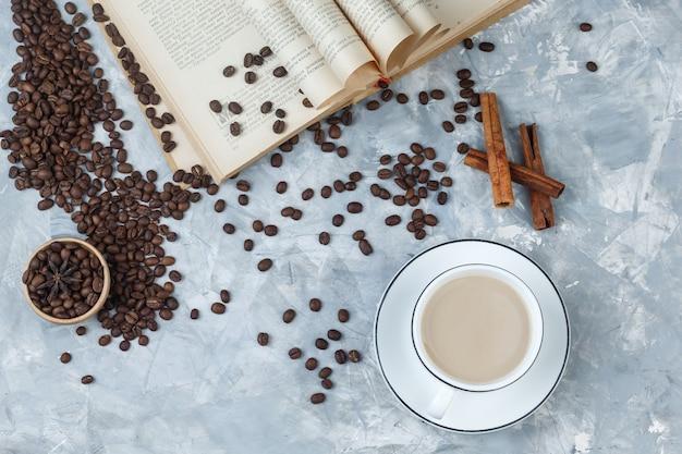 Café dans une tasse avec des grains de café, livre, bâtons de cannelle vue de dessus sur un fond de plâtre gris