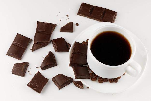 Café dans une tasse et morceaux de chocolat sur une surface blanche