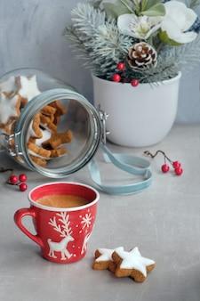 Café dans une tasse de noël rouge et de délicieux biscuits au gingembre étoilé dans un bocal en verre avec des décorations d'hiver