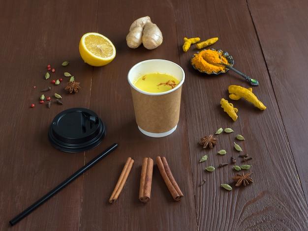 Café dans une tasse en papier avec curcuma, cannelle, gingembre, citron et poivre. prévention des infections antivirales. espace copie, vue de dessus
