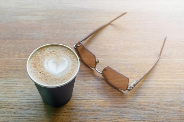 Café dans une tasse en papier avec forme de coeur sur sa surface. vue de dessus du cappuccino à emporter avec des lunettes de soleil. stock photo