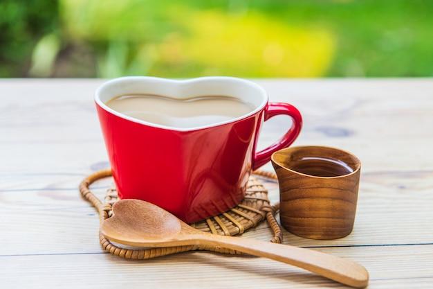 Café dans la tasse rouge et gâteau au chocolat pour le petit déjeuner dans le jardin.