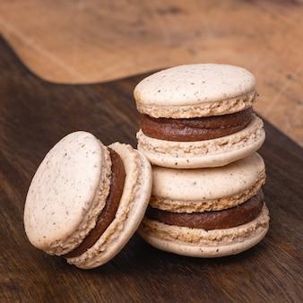 Café dans une tasse en verre et macarons au chocolat sur fond en bois. composition d'automne confortable - image