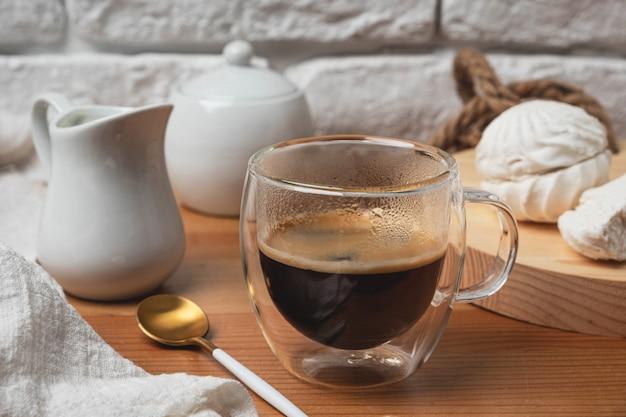 Café dans une tasse en verre sur une table en bois contre un mur de briques blanches.
