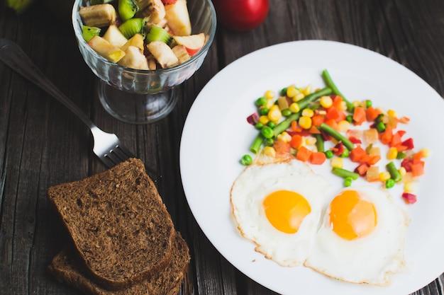 Café dans une tasse verte sur une surface en bois avec de la nourriture, délicieux petit déjeuner