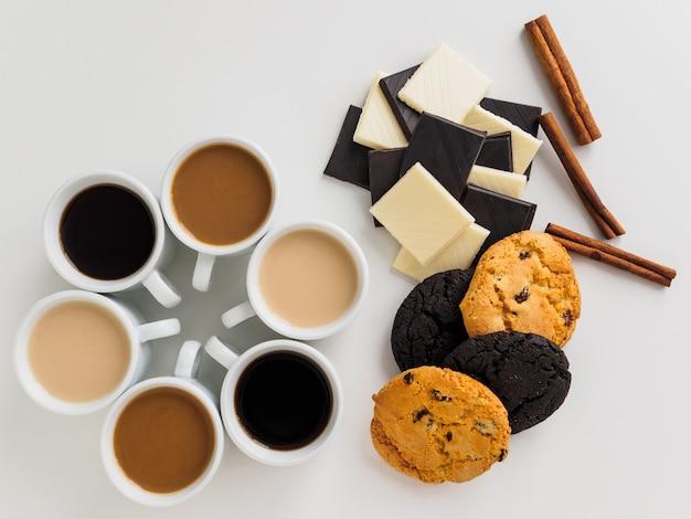 Café dans des tasses blanches en cercle et beaucoup de bonbons