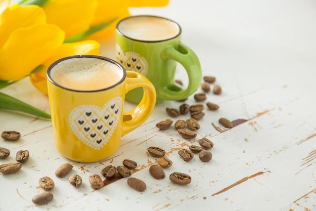 Café dans des tasses vertes et jaunes, tulipes