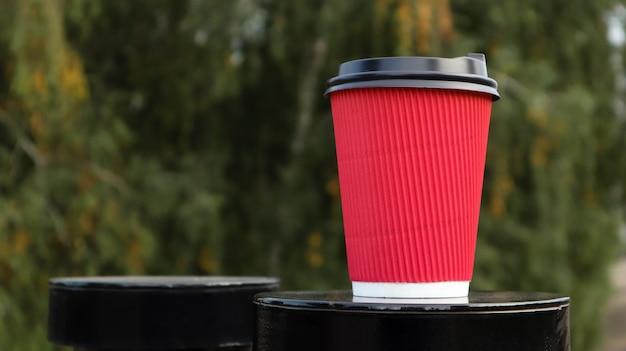 Café dans un verre écologique jetable en papier de couleur rouge avec un couvercle en plastique noir sur fond de parc verdoyant. mise au point sélective. fermer