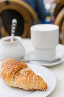 Café délicieux avec croissant. concept de petit-déjeuner français. tasse de café sur la table en plein air à la terrasse du café
