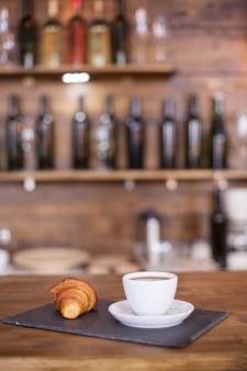 Café délicieux et croissant savoureux avec des bouteilles de vin floues en arrière-plan. vieux vin. petit déjeuner délicieux.