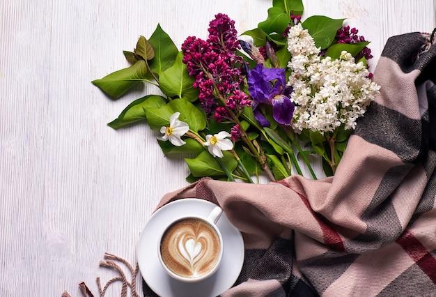 Café et différentes fleurs lilas sur fond blanc