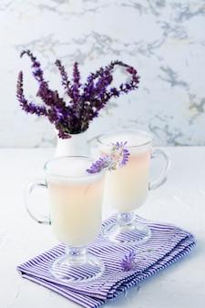 Café avec du lait, de la mousse et de la lavande dans des verres et un bouquet de fleurs dans une cruche sur une table blanche. vue verticale