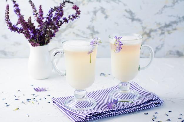 Café avec du lait, de la mousse et de la lavande dans des verres et un bouquet de fleurs dans une cruche sur une table blanche