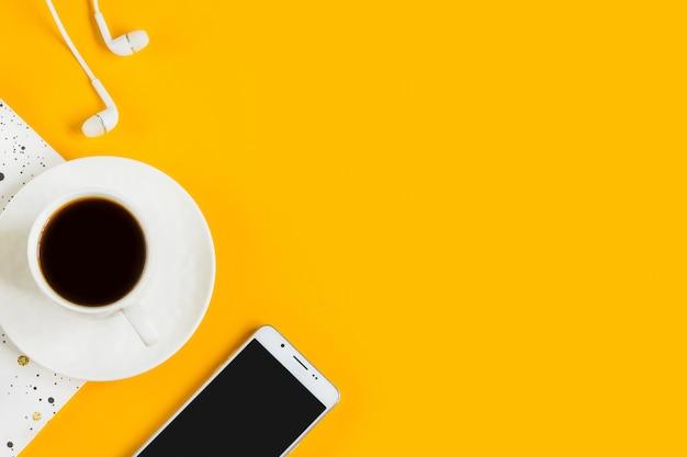 Café du matin, cahier, téléphone portable, plantes sur fond jaune. fond jaune d'affaires.