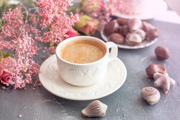Café du matin dans une tasse blanche avec des coquillages.