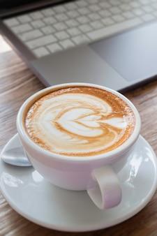 Café du matin latte sur le bureau en bois de bureau à domicile,