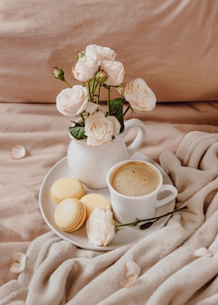 Café du matin avec macarons et fleurs