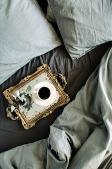 Café du matin sur plateau vintage doré au lit avec drap gris et oreillers