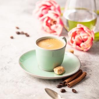 Café du matin et tulipes de printemps sur gris clair