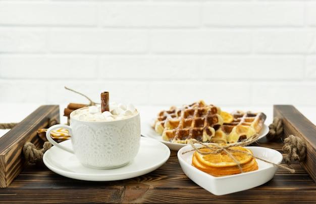 Café du petit déjeuner tôt avec des guimauves et un bâton de cannelle et gaufres belges se trouvent sur un plateau en bois