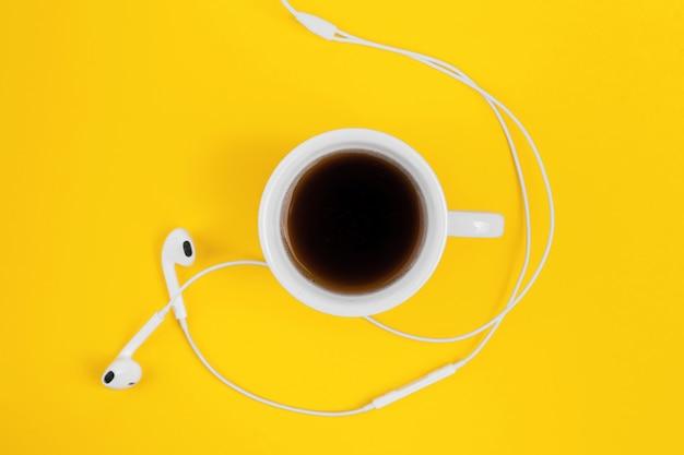 Café et écouteurs sur fond jaune.